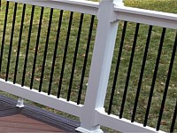 <b>Black aluminum balusters are a great addition to your new deck railing. They almost disappear when you are looking through to your view. Also shown here are feature boards in a different color on the deck. </b>