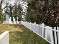 <b>5' high white pvc picket fence in contemporary style with pointed pickets and new england post caps with a concave pattern</b>