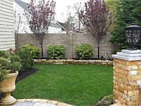 <b>Brown Granite Ecostone Simtek Fence in backyard</b>