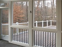 <b>Interior shot of a screened porch with composite deck boards, white composite railing and black aluminum balusters. Showing the handcrafted aluminum screen door as the exit onto the deck. All beams and supports are wrapped and a downward illuminated deck rail light is shown on one of the supports. Exterior posts have post cap lights to illuminate the night.</b>