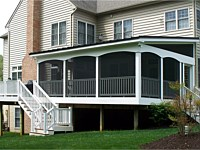 <b>Screened Porch with a shed style roof, complete with composite deck boards and white vinyl railing. An arched finish was given to the vinyl wrap on the exterior perimeter of the room. The screening system includes Screeneze and Super Screen Mesh.</b>