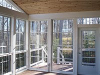 <b>View from the inside of the screened porch. This photo highlights the Eze-Breeze sliding panel system that allows you to use your room all year round. Even the door has an Eze-Breeze vertical four track system. The structure has composite deck boards, white vinyl railing with black aluminum balusters. The ceiling of the screened porch is finished in tongue and groove cedar, and all the support beams are wrapped in low maintenance vinyl. You can also see an electrical outlet was installed for electricity needs inside the room.</b>