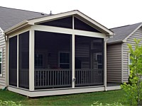 <b>Screened Porch with a gable style roof, complete with composite deck boards and tan vinyl railing and balusters. You can see an electrical outlet was installed on the exterior of the structure for ease in accessing power when outside of the home.</b>