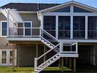 <b>Screened porch and deck with composite deck boards and white vinyl railing with black balusters. The screened porch has a gable style roof and is screened with Eze-Breeze sliding panel system that allows you to use your room all year round. The deck has a decorative trellis with lattice.</b>